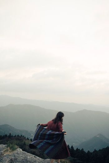 Woman sitting on landscape against mountain range
