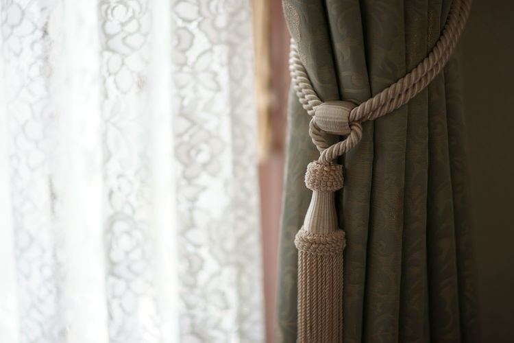 Curtain with tassel hanging at home