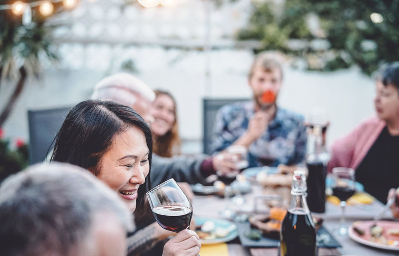 Smiling woman drinking red wine while sitting with friends at dining table
