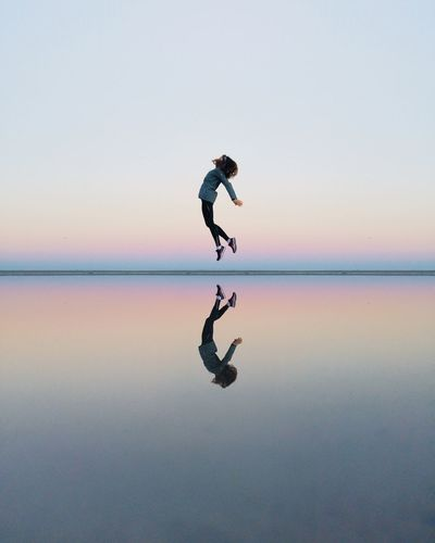 Full length of woman jumping on beach against sky during sunset