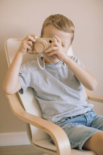 Full length portrait of boy sitting at home