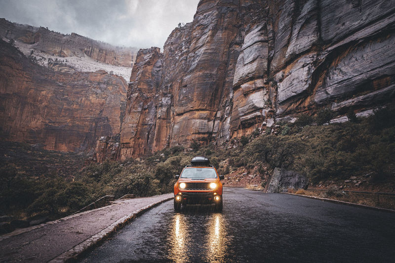 Car on road by rock formation