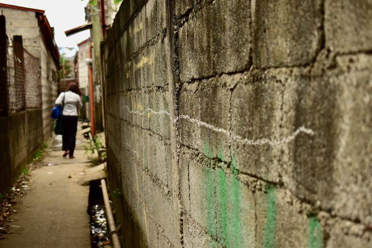 Rear view of man walking in alley