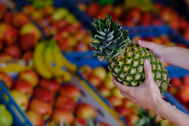An Ananas in front of vegetables on a market. Close-up Day Flower Focus On Foreground Food Food And Drink Freshness Fruit Healthy Eating Holding Human Body Part Human Hand Market Men One Person Outdoors People Real People Retail