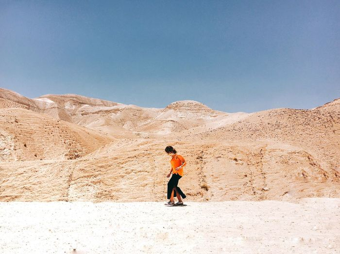 Woman Walking Against Mountains At Desert During Sunny Day