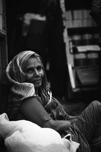 Side View Portrait Of Senior Woman Sitting By Plastic Bag