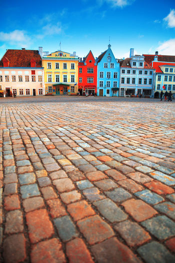 Surface level of cobblestone street by buildings in city