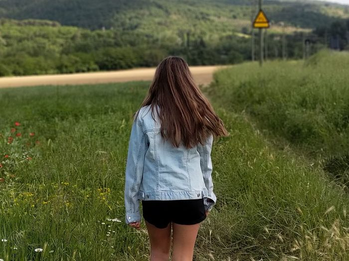 Rear view of girl standing on grassy field