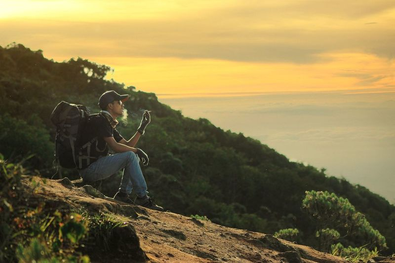 Side view of man smoking while sitting on mountain against sky during sunset