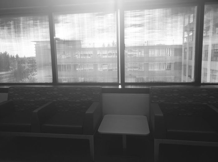 Waiting Room Chairs Windows Looking Out The Window Looking Outside Black And White Black & White Black And White Photography No People Indoors  Building Interrior Buildings In Background Greyscale Rows Of Windows Grey Sky Window Shade Seats Row Bright Sun