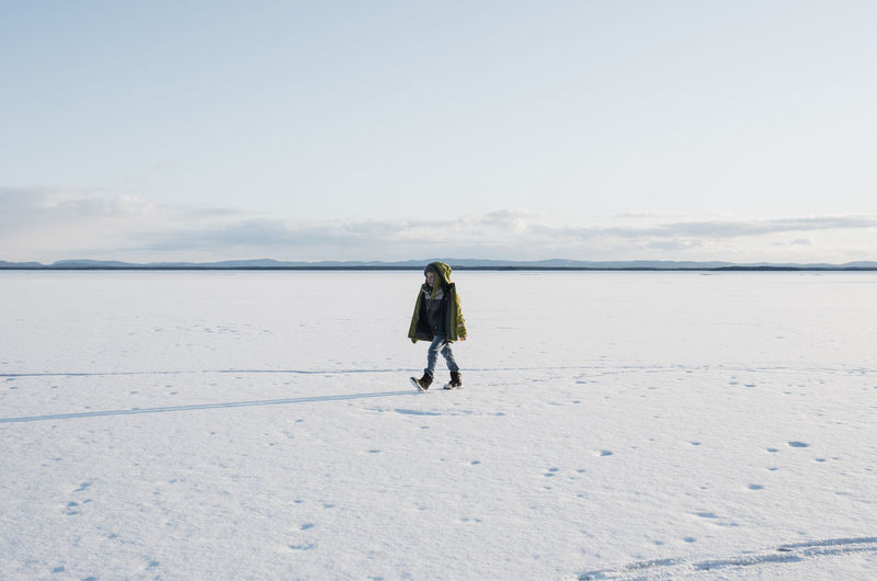 Full length rear view of man on snow covered land
