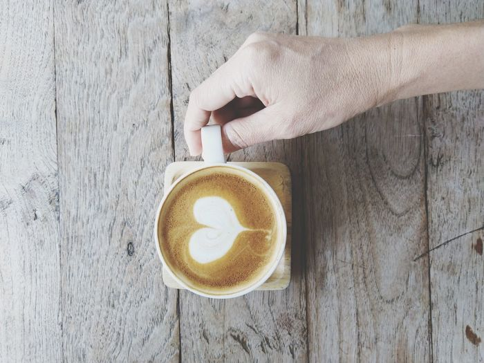 latte art Human Hand Froth Art Cappuccino Frothy Drink Drink Latte Directly Above Coffee - Drink Table Holding Hot Drink