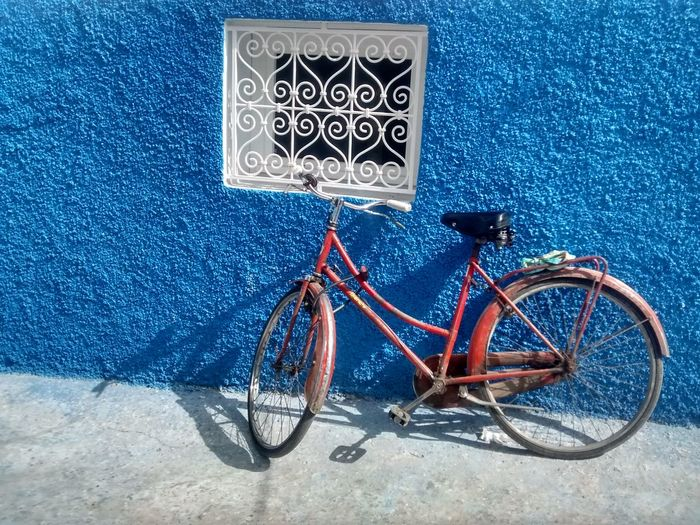 Bicycle Parked Against Blue Wall