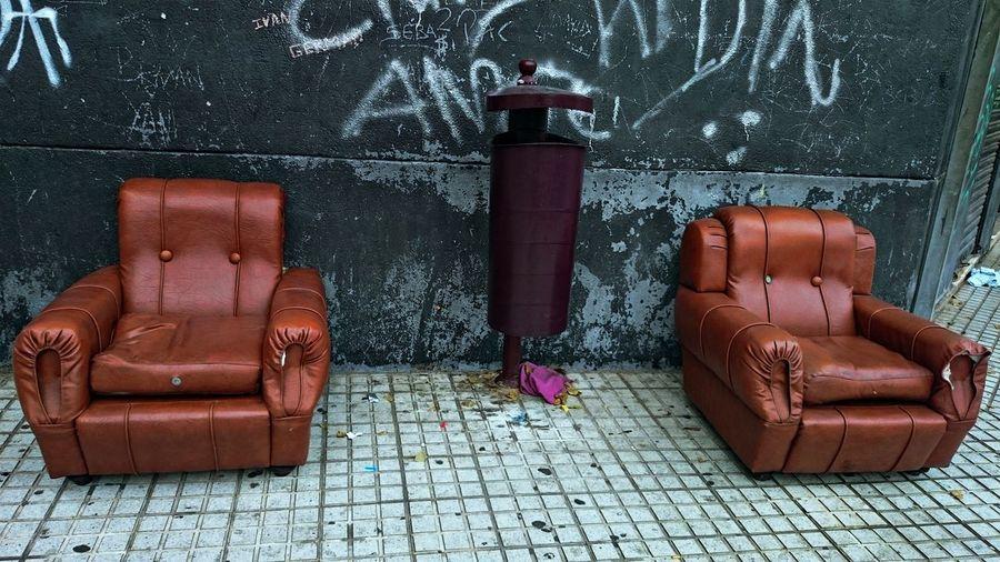 Dust Bin Amidst Weathered Sofas On Sidewalk Against Wall