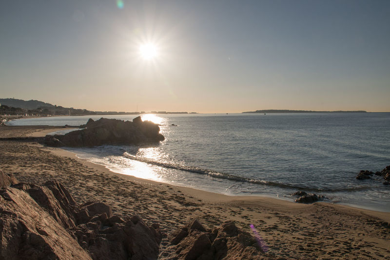 sunrise over the bay of Cannes French Riviera Sea Sea And Sky Sun Sunset Water Beach Sky Land Beauty In Nature Scenics - Nature Nature Rock Sunlight Tranquility Wave Solid Tranquil Scene Rock - Object Motion Horizon Over Water Lens Flare Outdoors No People Bright