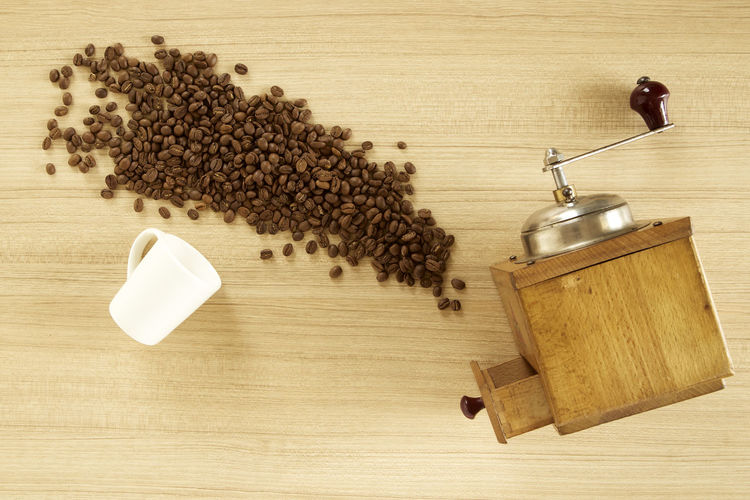 High angle view of coffee beans with grinder on wooden table