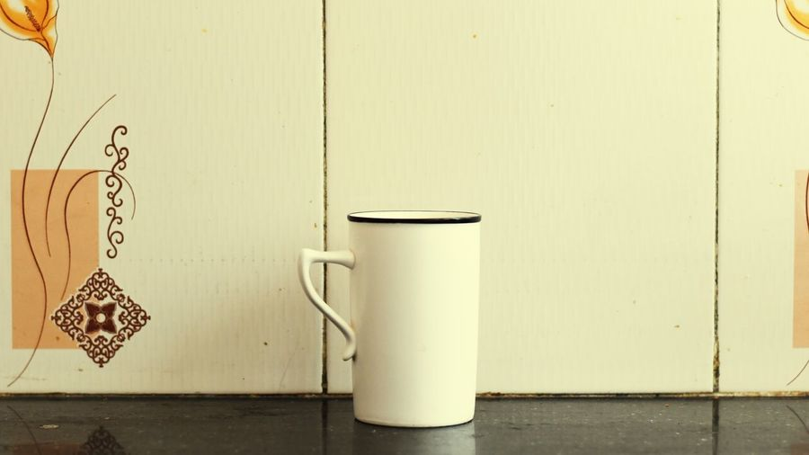 Close-up of coffee cup on table against white wall