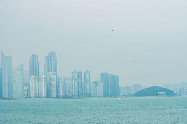 Urban skyline by sea against sky