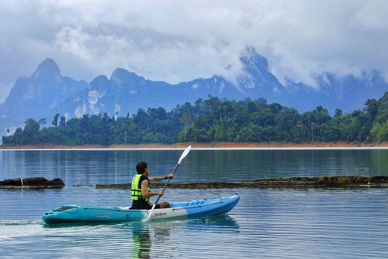kayaking in dam Mountain Water Sky Nautical Vessel Real People Nature Outdoors Cloud - Sky Tree Lake Oar Mode Of Transport Beauty In Nature Leisure Activity Scenics Day Transportation One Person Men Lifestyles Kayaking Riverside