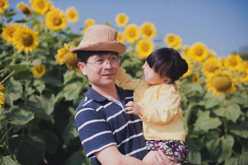 Man holding daughter against sunflowers