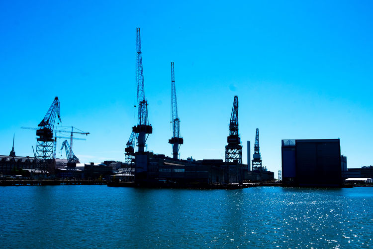 Cranes at commercial dock against blue sky
