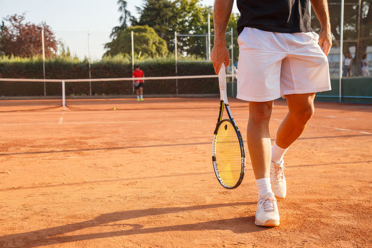 Low section of young man walking with racket at tennis court