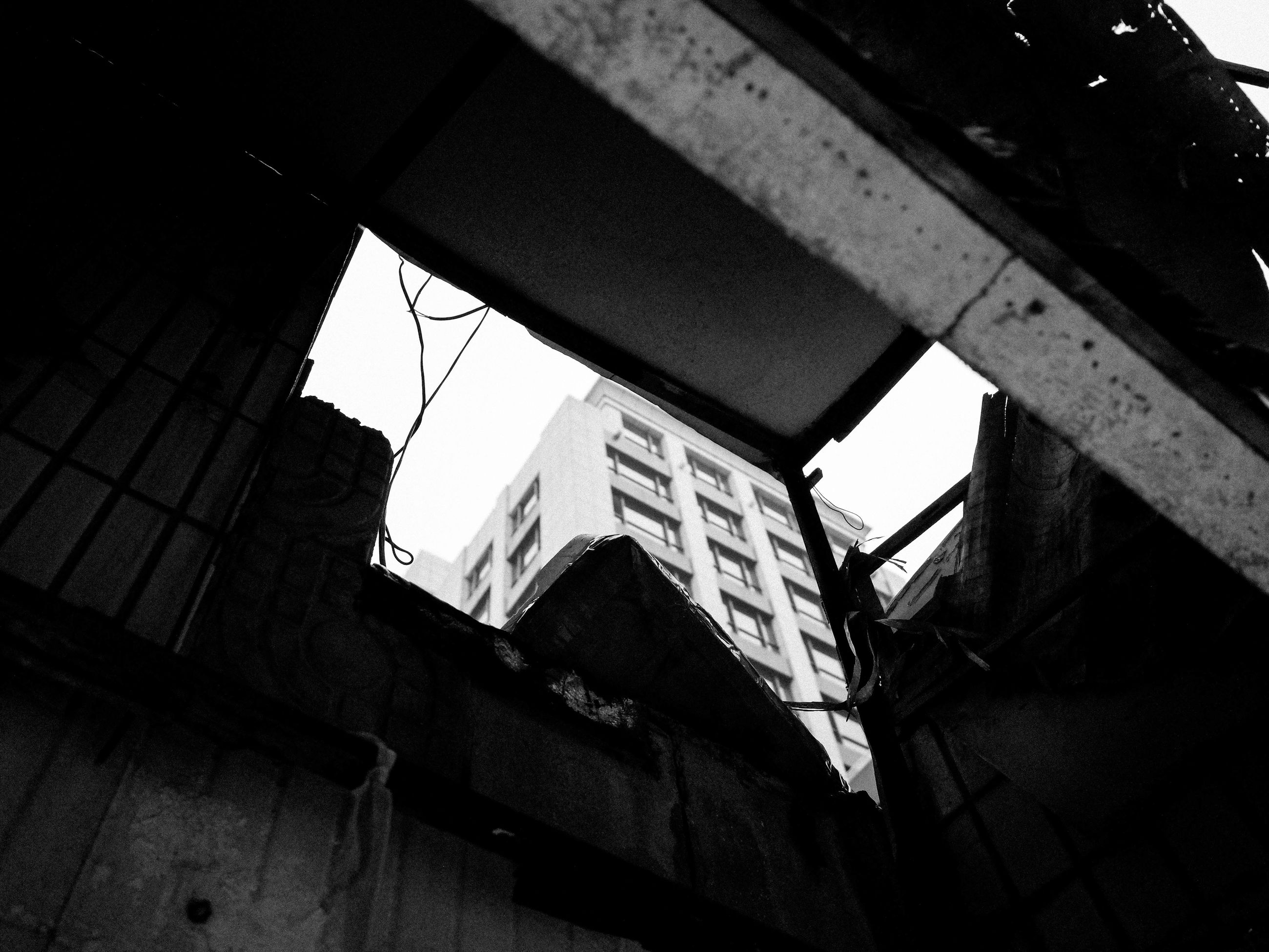 architecture, built structure, low angle view, building exterior, building, sky, window, residential building, clear sky, city, old, no people, day, outdoors, abandoned, residential structure, damaged, sunlight, tilt, shadow