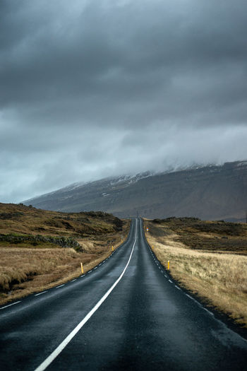 Empty road along landscape against cloudy sky