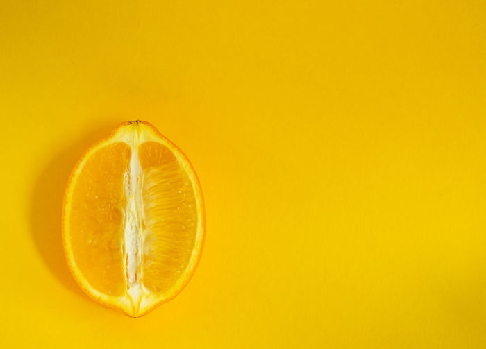 Lemon Healthy Eating Yellow Colored Background Citrus Fruit Food And Drink Studio Shot SLICE Fruit Food Copy Space Wellbeing No People Orange Color Indoors  Freshness Single Object Yellow Background Simplicity Cross Section Close-up Orange Ripe Vitamin C Sour Taste