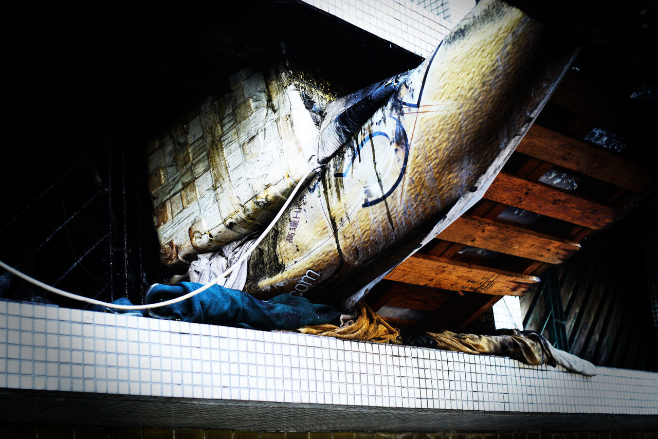 HIGH ANGLE VIEW OF CAT SLEEPING IN ABANDONED BUILDING