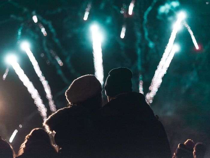 Rear View Of Couple Looking At Firework Display