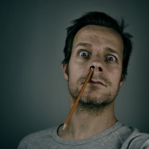 Portrait Of Man With Pencil In Nose Against Wall