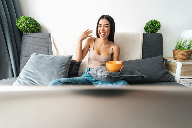 Mid adult woman sitting on sofa at home