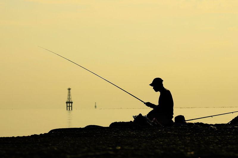 Silhouette man fishing at sunset