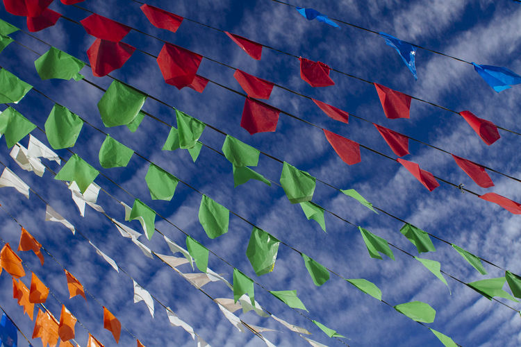 Low angle view of decoration flags against cloudy sky