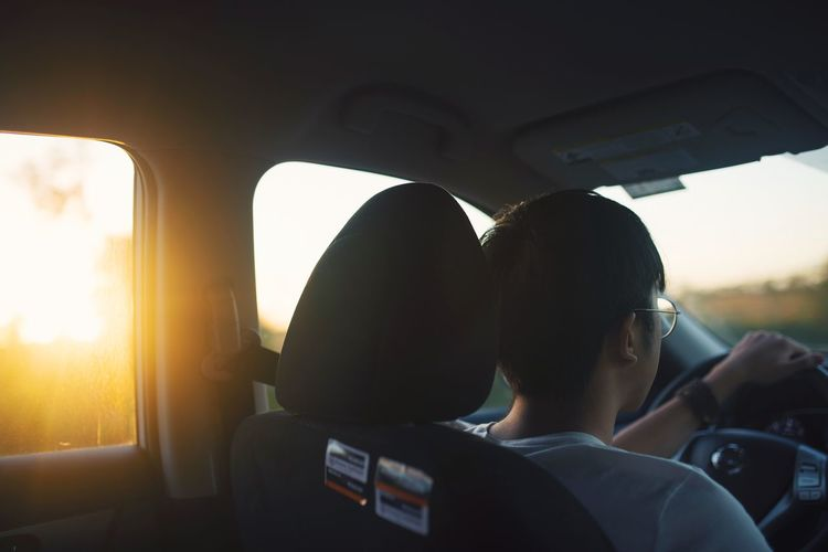 Rear view of man sitting in car