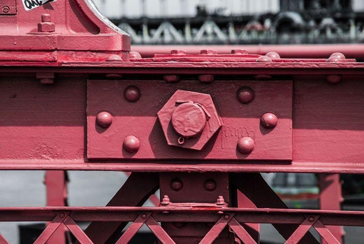 Close-up of red cropped of metallic bridge