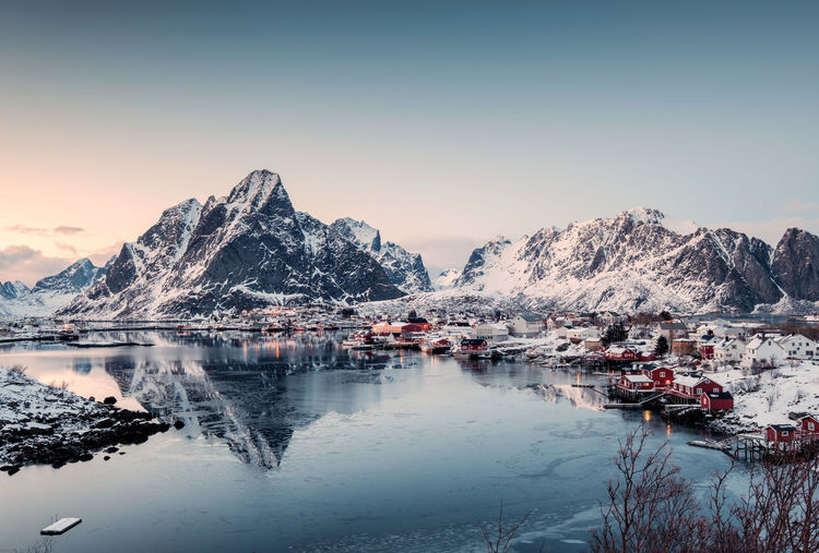 Viewpoint of Fishing village in valley on winter at Reine, Lofoten islands, Norway Water Sky Scenics - Nature Beauty In Nature Reflection Cold Temperature Mountain Winter Tranquility Nature Tranquil Scene Waterfront Snow No People Idyllic Lake Sunset Clear Sky Snowcapped Mountain