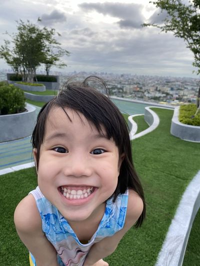 Portrait of smiling girl against sky