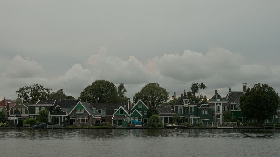 Houses and trees by lake against sky