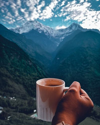 Cropped hand holding coffee mug against mountains