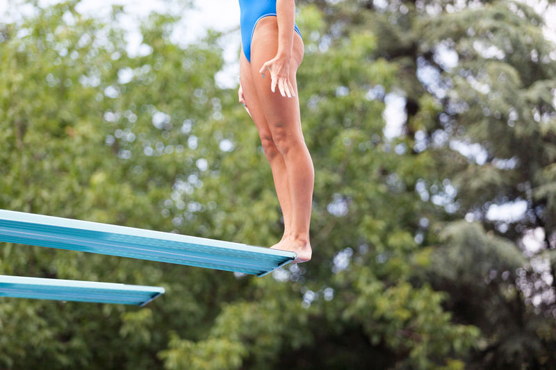Female high diver standing on a springboard, preparing to dive Diving Jump Recreation  Standing Woman Dive Diving Board Female Fitness Girl Human Leg Human Legs Jumping Lifestyles Nature Outdoors Pool Sport Springboard Summer Swimming Pool Tree Vacation