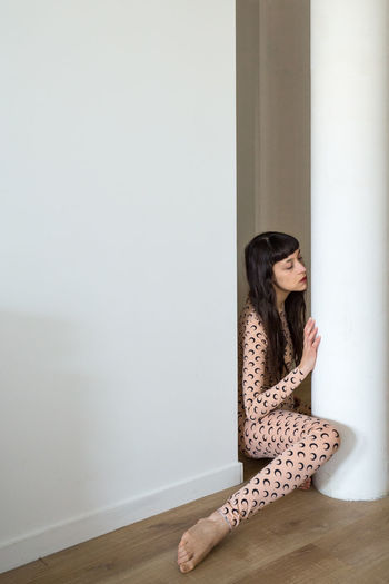 Woman sitting against wall at home