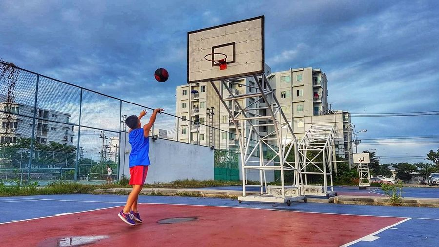 Rear view of man playing basketball hoop against sky