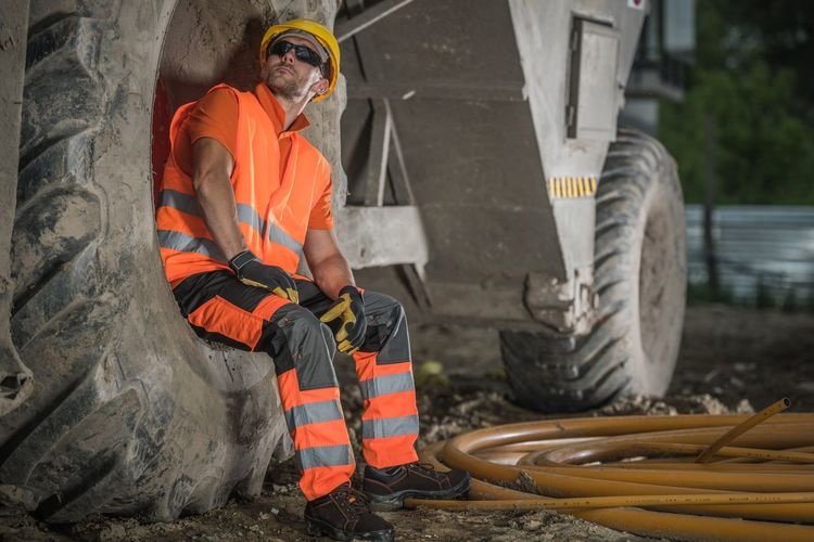 Worker sitting on tire of bulldozer at construction site