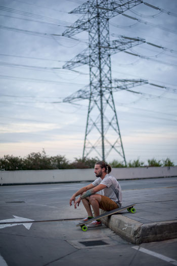 Man sitting on road against sky