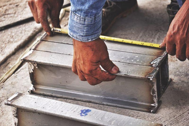 Cropped hands manual workers measuring metal at workshop