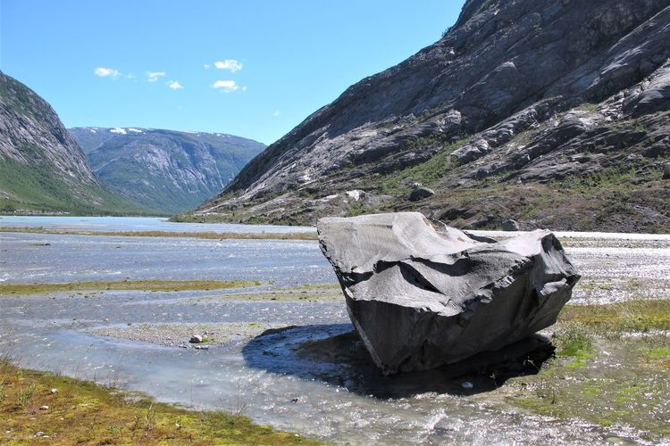A boulder on the lake shore under the Nigardsbreen glacier in Norway Jostedalsbreen Nigardsbreen Sunny Boulder Day Environment Idyllic Lake Landscape Mountain Mountain Range Nature No People Non-urban Scene Outdoors Rock Rock - Object Scenics - Nature Sky Solid Tranquil Scene Tranquility Valley Water
