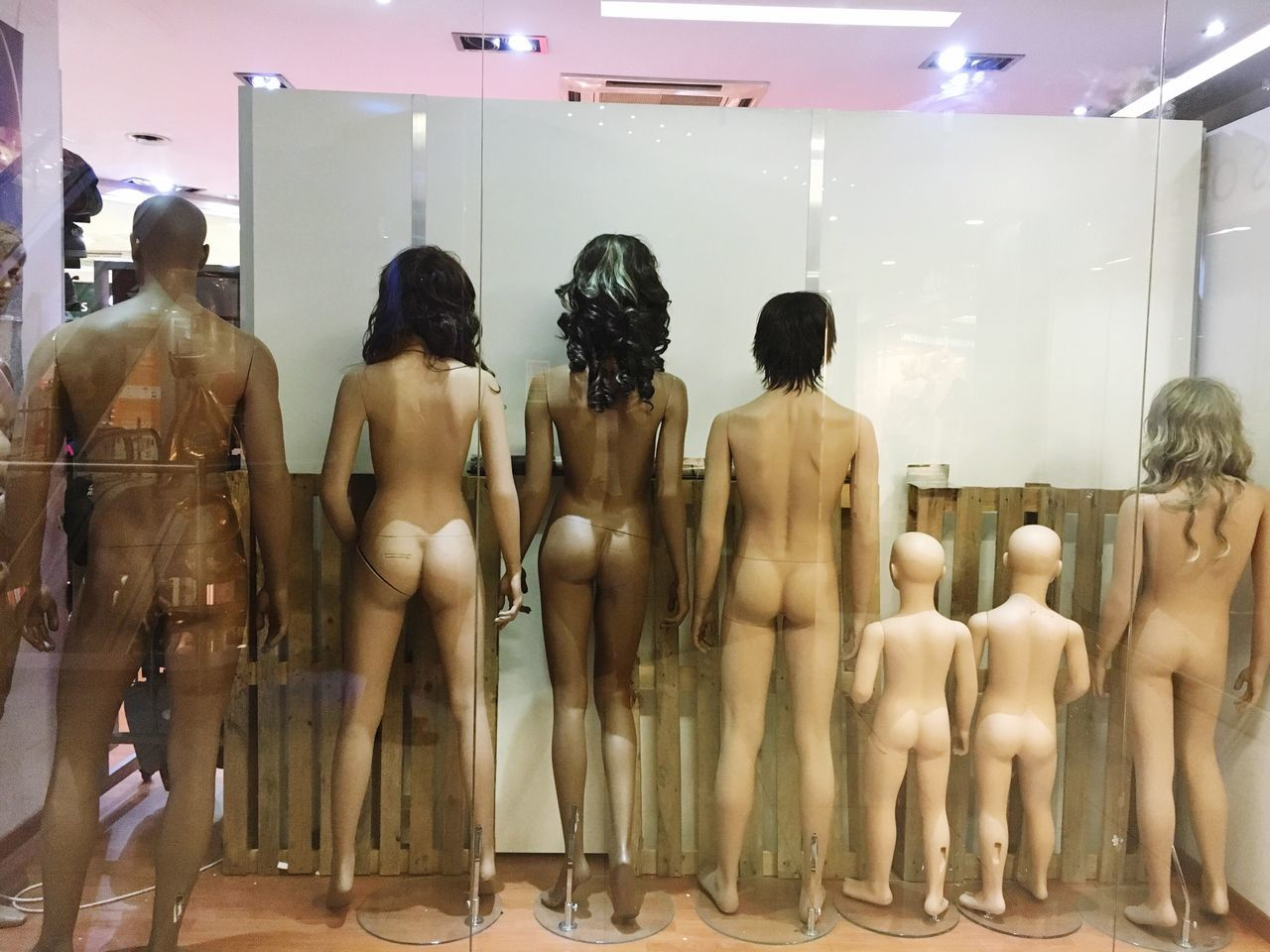 indoors, retail, in a row, men, human representation, for sale, store, art and craft, large group of objects, art, arrangement, hanging, shop, person, variation, rear view, market stall, market