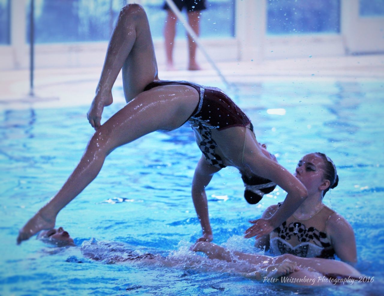 swimming pool, skill, real people, leisure activity, swimwear, water, two people, lifestyles, exercising, swimming, bikini, vitality, handstand, day, outdoors, wet, upside down, young women, strength, full length, flexibility, healthy lifestyle, sport, young adult, athlete, adult, people